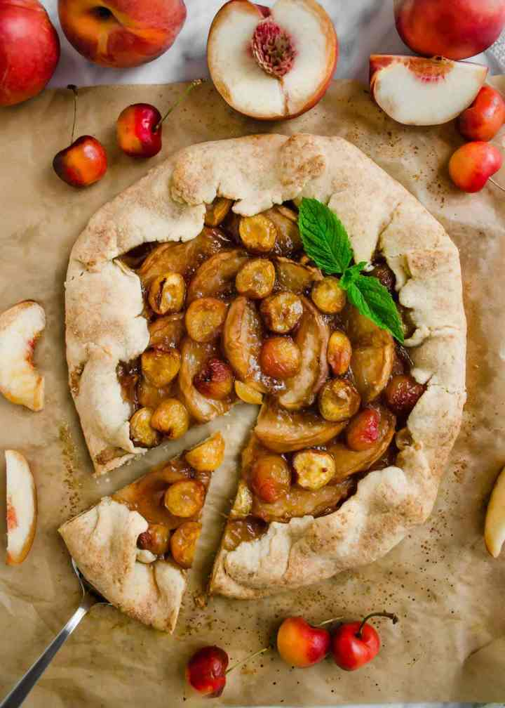 White Peach and Cherry Galette on parchment paper flatlay.