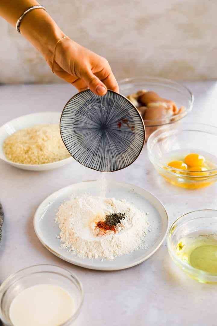 Hand pouring seasoning into flour for Chicken Katsu dredge mixture