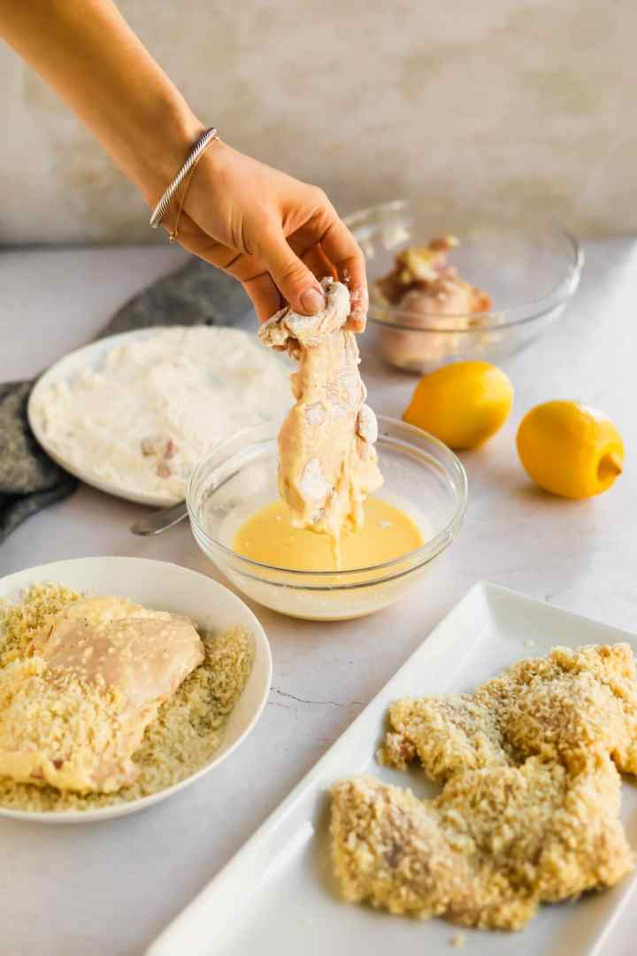 Raw chicken being dipped into egg mixture with lemons, flour, and panko
