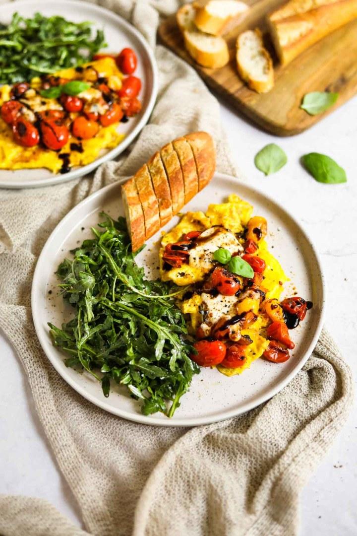 Soft-scrambled eggs with cheese (burrata), blistered cherry tomatoes, arugula salad, baguette, balsamic glaze