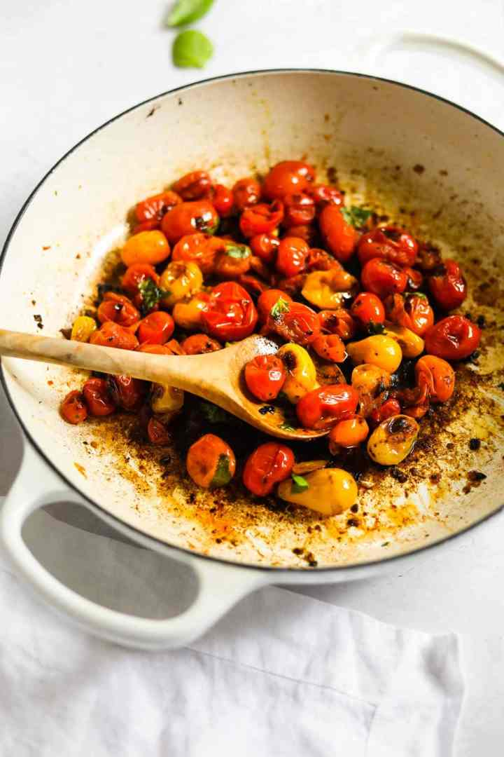 Blistered cherry tomatoes in a white Le Creuset braiser with a wooden spoon