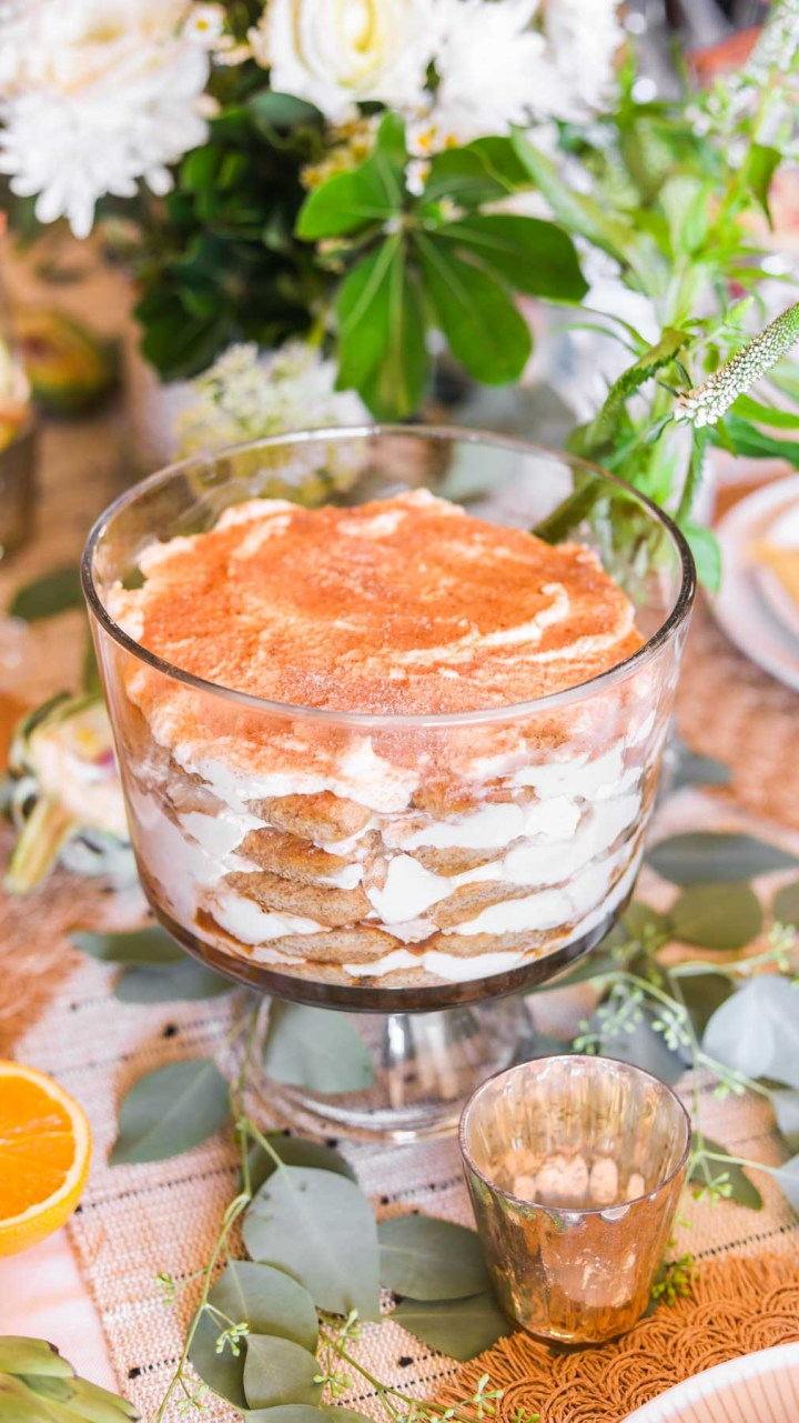 Tiramisu trifle on top of tablecloth with green and white flowers