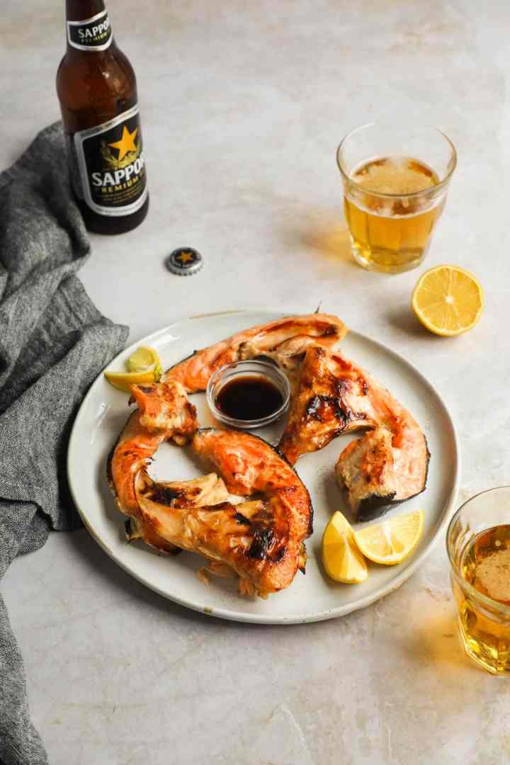 Broiled Salmon Collars (Sake Kama) with Sapporo Beer and lemon.