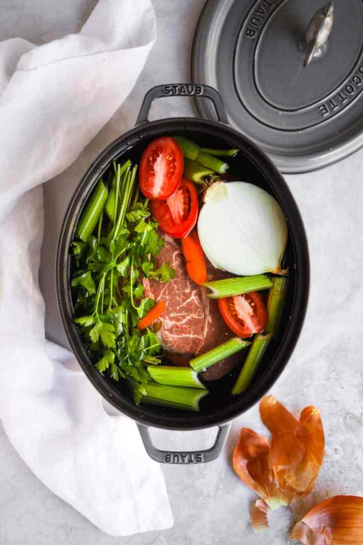 Italian beef soup ingredients in graphite Staub dutch oven.