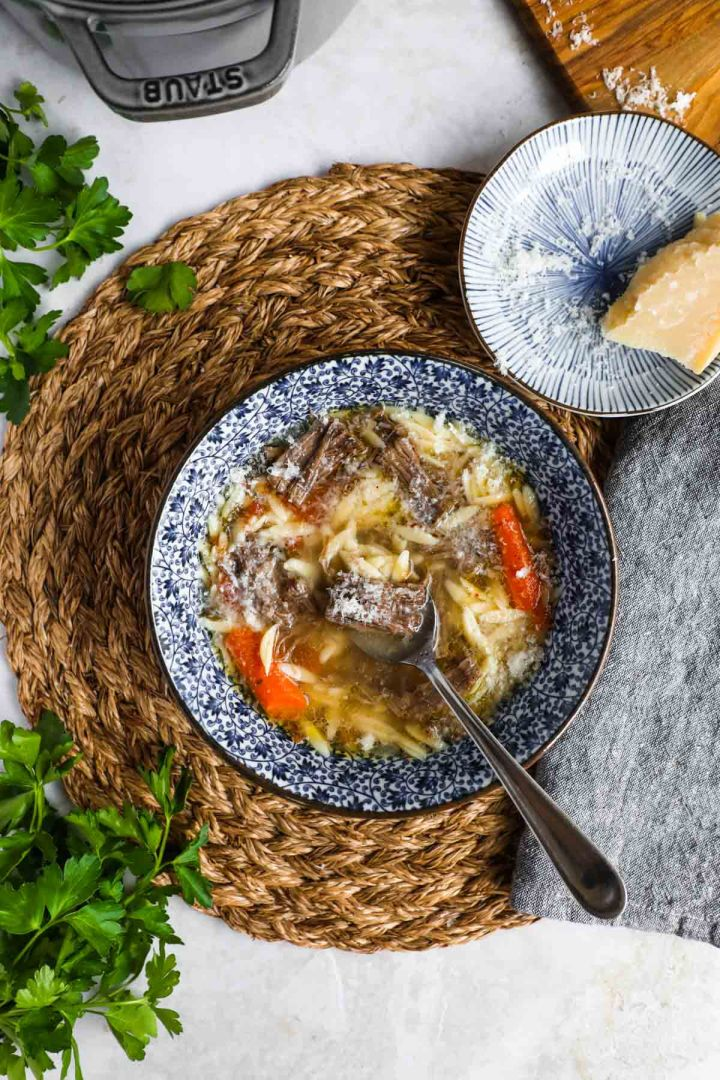 Italian beef soup (brodo di carne) in blue and white bowl with Parmigiano-Reggiano on side.