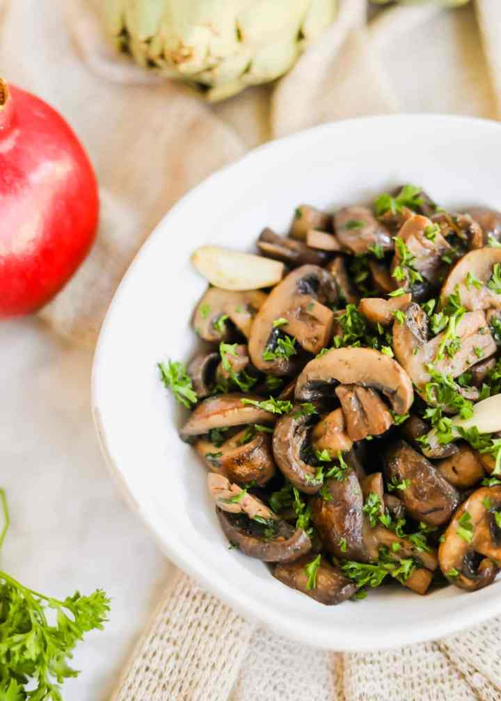 Sautéed mushrooms with White Wine in white bowl with parsley, garlic, and seasoning.