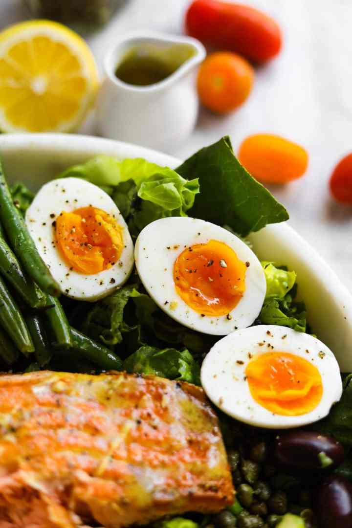 Soft Boiled Jammy Eggs in a salad bowl with tuna and lemon, tomatoes, and dressing in background.