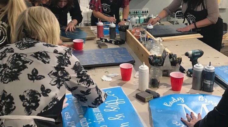 Adults making custom wood signs at a DIY workshop