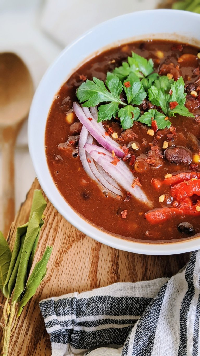 close up of high protein chili bowl with sliced red onion cilantro and bell peppers to garnish the vegan chili bowl recipe with tvp