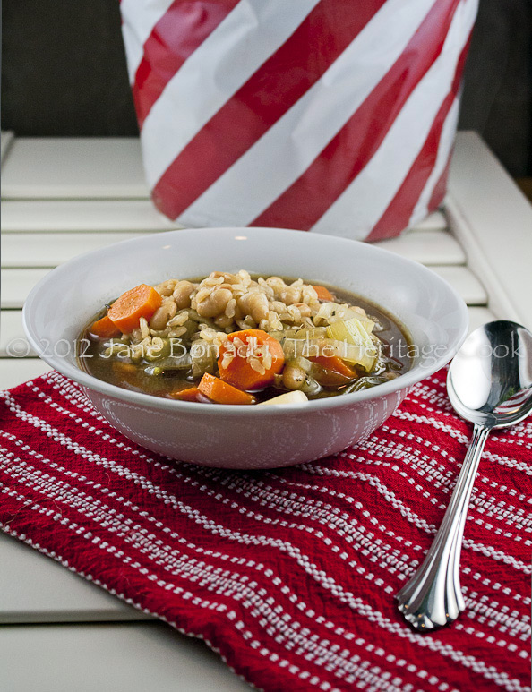 Bowl of soup on deep red towel with candy-stripe pot of rosemary in background