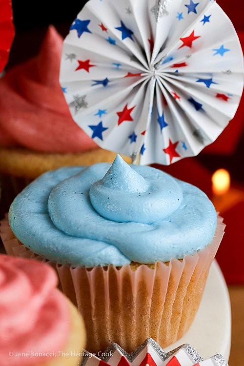 Vanilla cupcakes with blue tinted buttercream frosting and 4th of July decorations