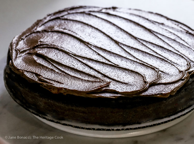 Beautifully back-lit frosted cake; Dark Chocolate Bourbon Cake with Whipped Ganache Frosting (Gluten-Free) © 2017 Jane Bonacci, The Heritage Cook
