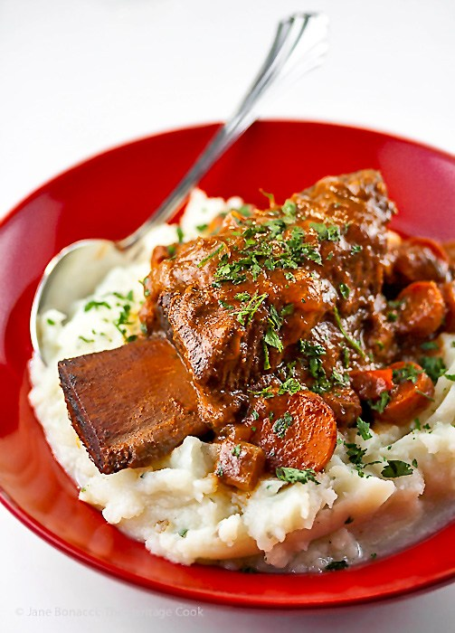 Red bowl filled with mashed potatoes and braised short ribs; 30 Warming Comfort Foods for Chilly Winter Days 2017 Jane Bonacci, The Heritage Cook