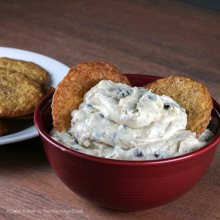 bowl of cheesecake dip with 2 cookies and plate of cookies behind; Chocolate Chip Toffee Cheesecake Cookie Dip © 2018 Jane Bonacci, The Heritage Cook