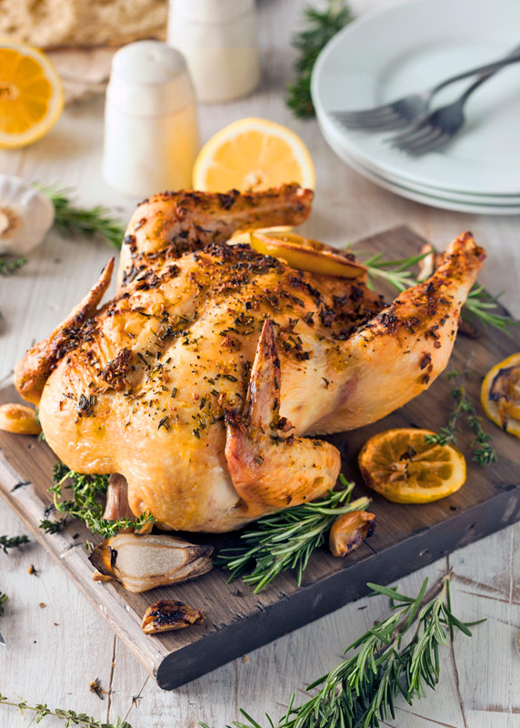 whole chicken on a board with lemon slices around; Lemon and Cumin Scented Chicken from The Heritage Cook 2018 Jane Bonacci, The Heritage Cook