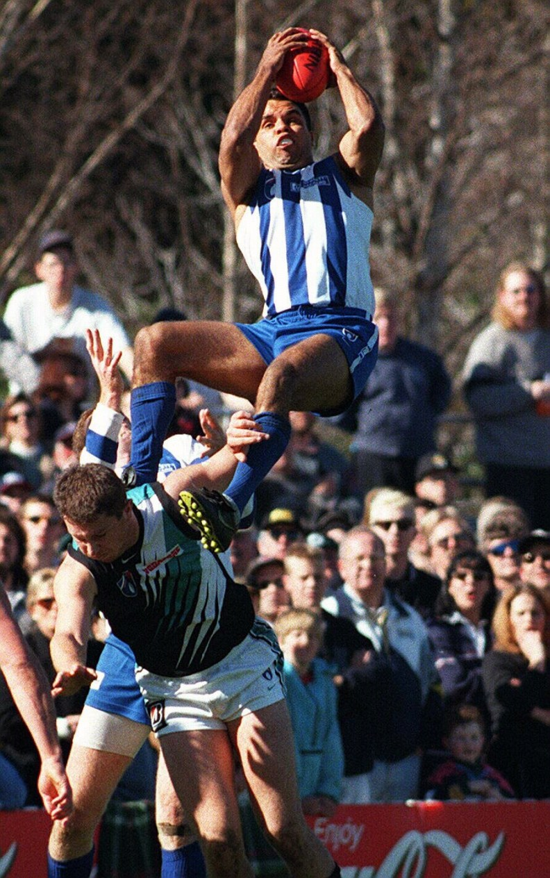 1Aug98 North Melbourne vs Port Adelaide at Manuka Oval. North Melbourne's Winston Abraham takes a spectacular mark over Port Adelaide's Brendon Lade.  a/ct/Football
