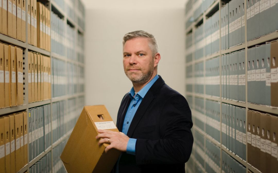 John standing in between archive shelves at the Tillburh archives, holding a box of documents.