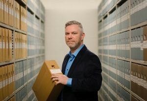 John standing in between archive shelves at the Tilburg archives, holding a box of documents.