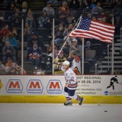 SPC Johnny Laursen carries the American flag on the ice in Cincinnati during intermission.