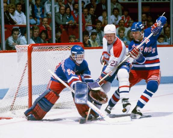 John Vanbiesbrouck pokes the puck away from Bob Gainey