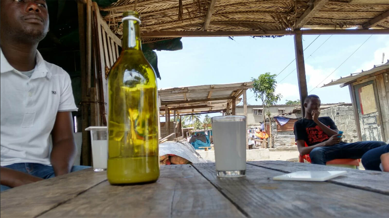 Drinking banji with locals in the Ivory Coast, one of the unique traditional alcoholic beverages to try while traveling abroad