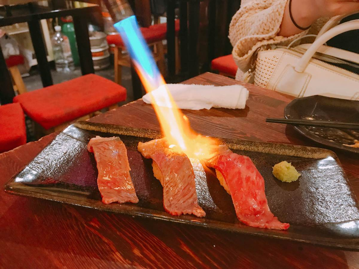 Eating Wagyu (Japanese beef) sushi while on a Shibuya bar hopping tour
