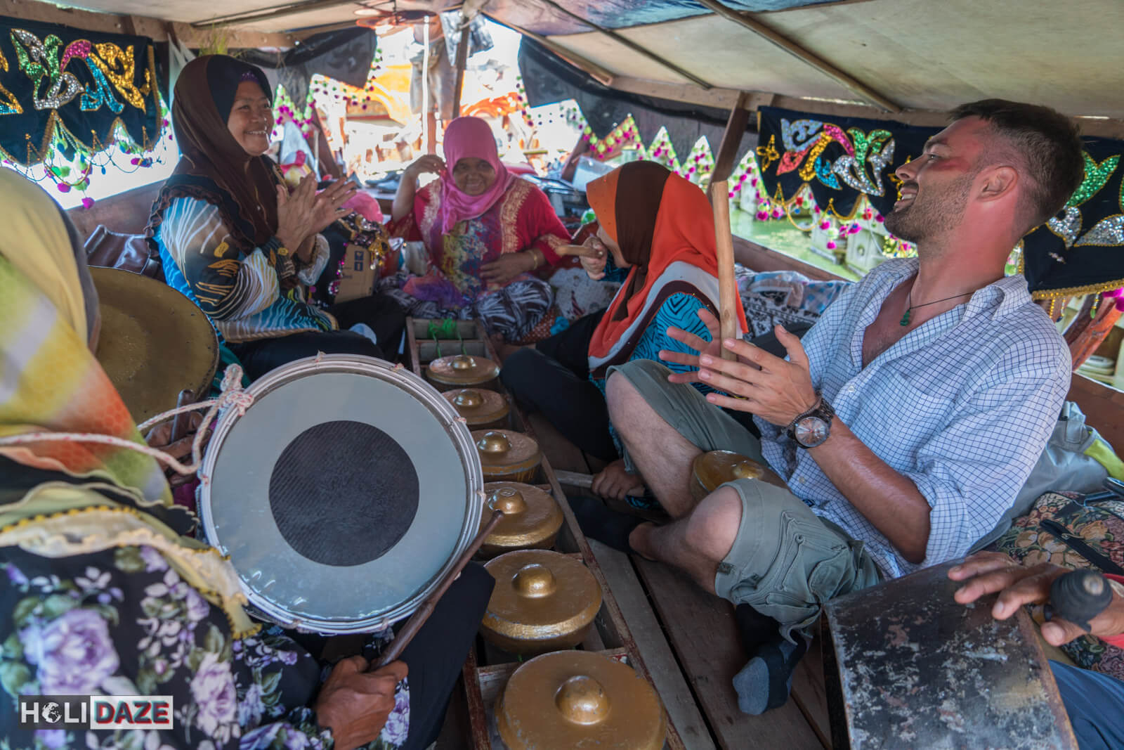 Derek Freal playing gamelan music aboard a boat at the Regatta Lepa festival in  Sabah