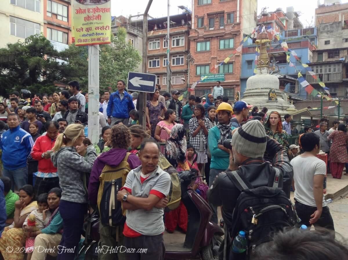 People in Kathmandu huddle in an open plaza in between aftershocks.