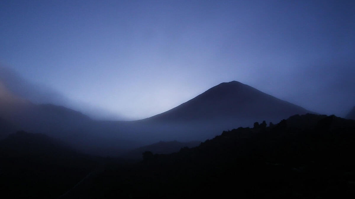 Ngauruhoe's ethereal silhouette looming from the mist as the sun rises