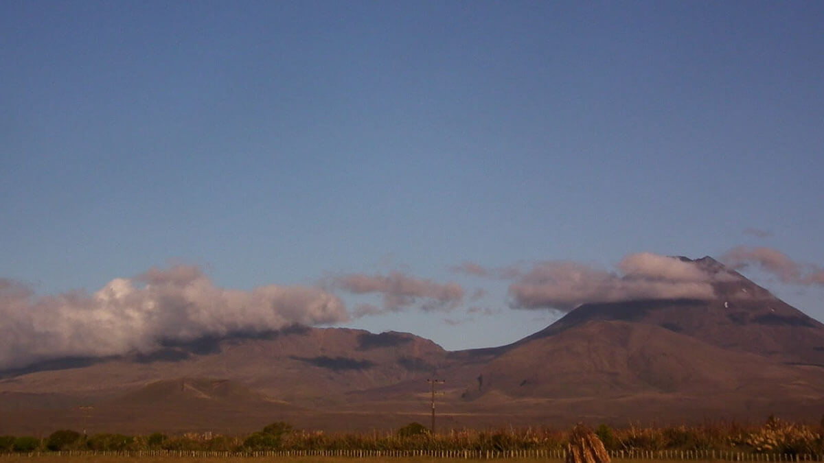 Mount Tongariro's head lost in the clouds on the left, while Mount Ngauruhoe stands proud to the right