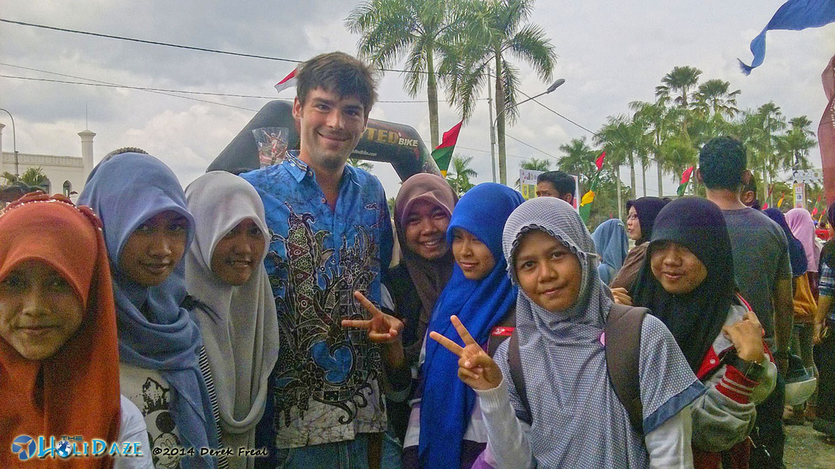 Local girls in Siak crowd around for a photo with a bule