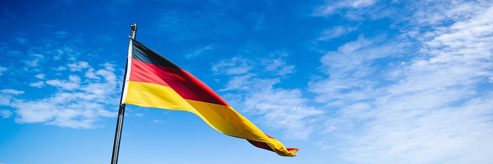German flag flying high over the blue skies of Berlin