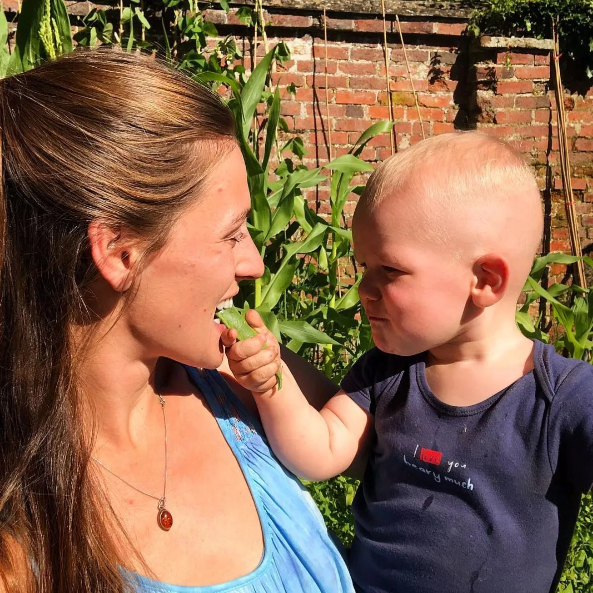 Adventurer Laura Bingham with son Ranulph eating homegrown beans from their vegetable patch at their home in Hallaton, Leicestershire