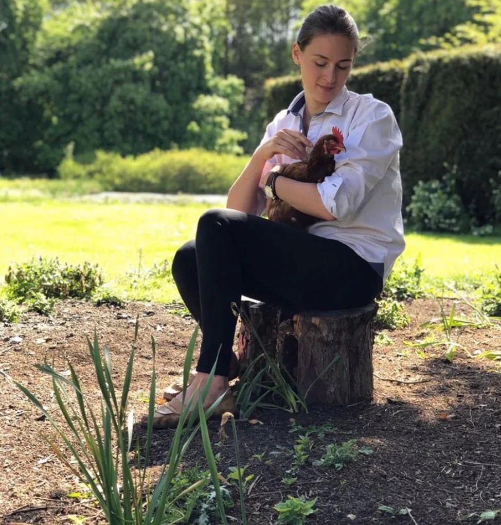 Laura Bingham with one of her chickens in the garden of her grade II listed home in Hallaton, Leicestershire