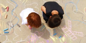 Children drawing with chalk on the sidewalk seen from overhead.