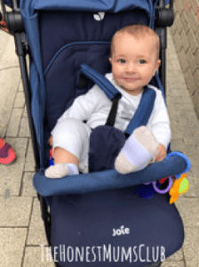 baby boy smiling in joie pact stroller in navy blazer colour