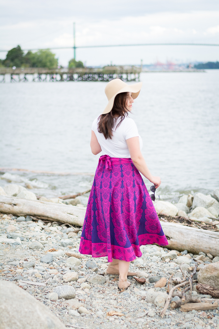 Woman poses on the beach in North Vancouver in Darn Good Yarn pink peacock print maxi skirt.