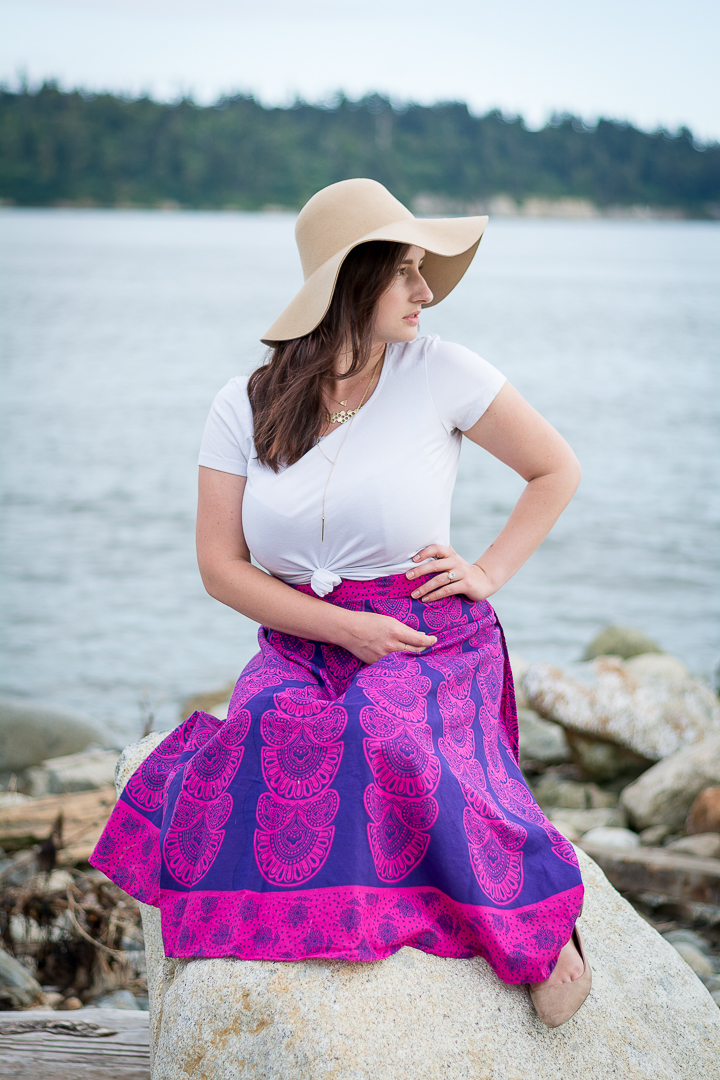 woman sits on the beach in pink maxi skirt and brown floppy hat