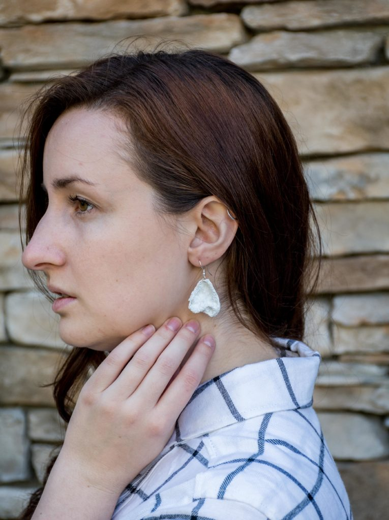 woman wears eco friendly earrings made out of recycled plastic bags