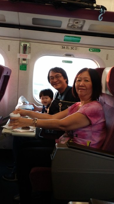 Our cheeky little girl is obviously very excited though she doesn't get her share of tea, coffee or cake.. oops! Notice the overhead compartment also allows strollers or luggages to be placed. Those roller types will be parked at a luggage area pretty near our seats.