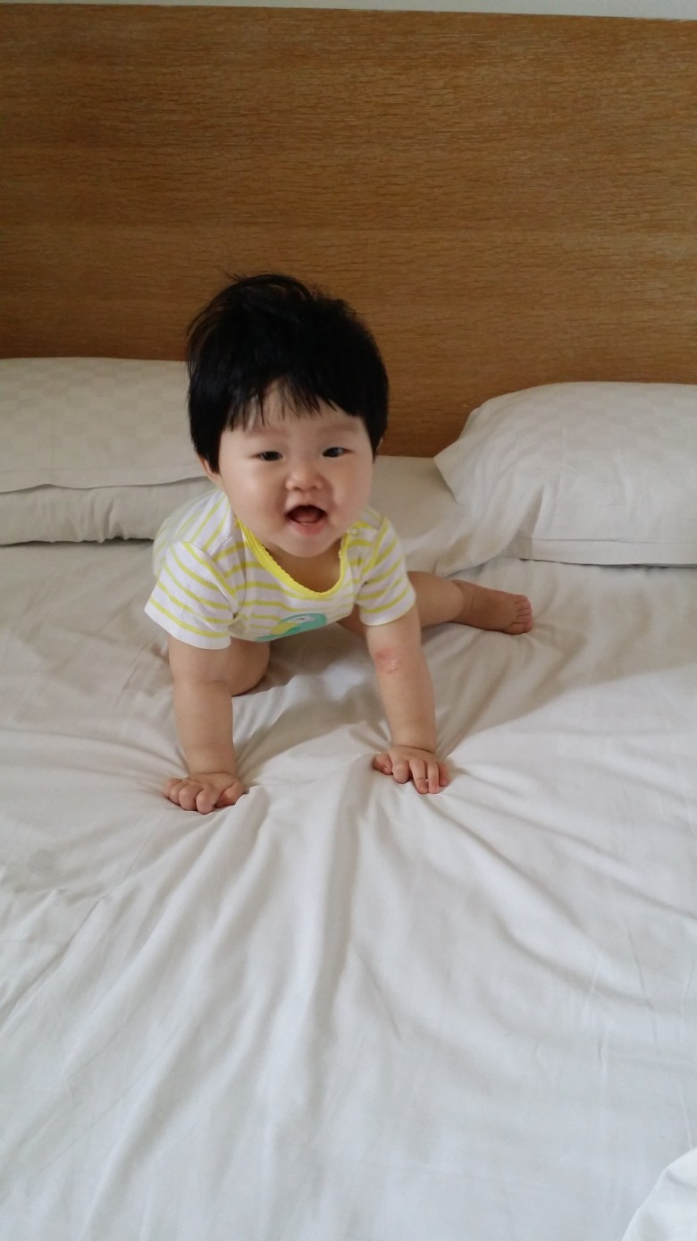 Happy baby on Beacon hotel bed Taichung