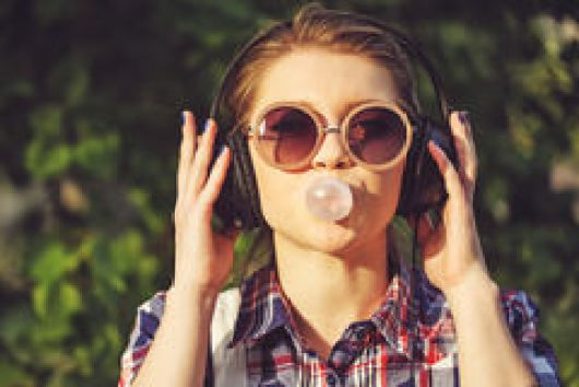 hipster-girl-listening-to-music-on-headphones-and-chews-the-cud-55635705.jpg