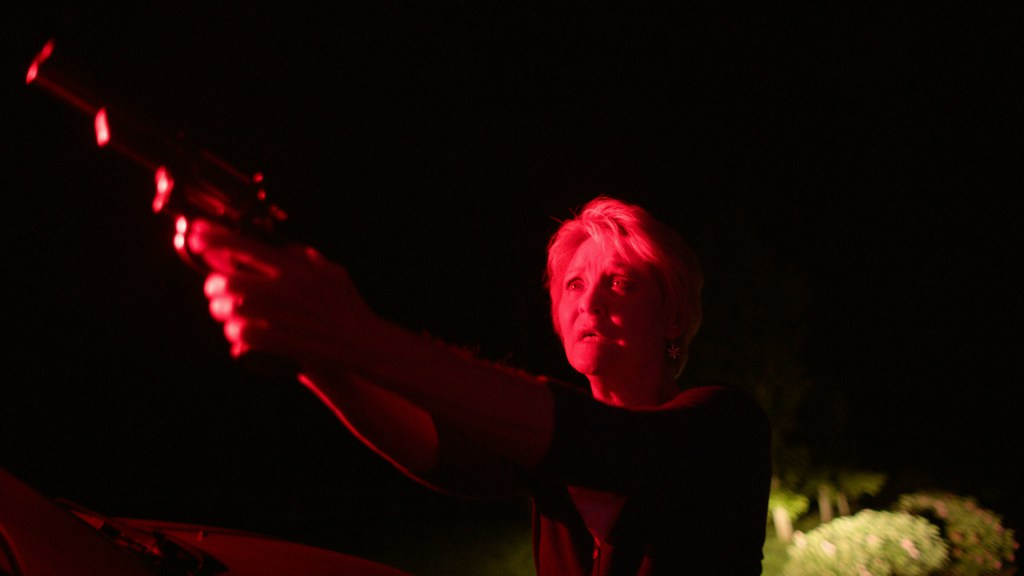 Dee-Wallace-with-Gun-in-Red-Light-Red-Christmas-Photo-by-Douglas-Burgdorff