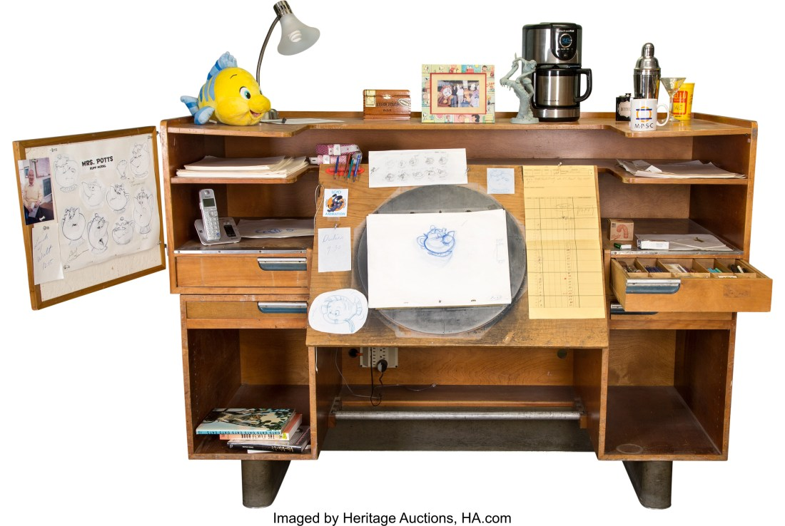 An animation desk designed by Kem Weber for the Walt Disney Company circa 1939 or 1940. It's shown here decorated with the accoutrements of a working animator, but the lot consists solely of the desk, the bulletin board, and a pencil tray that once belonged to Eric Larson.
