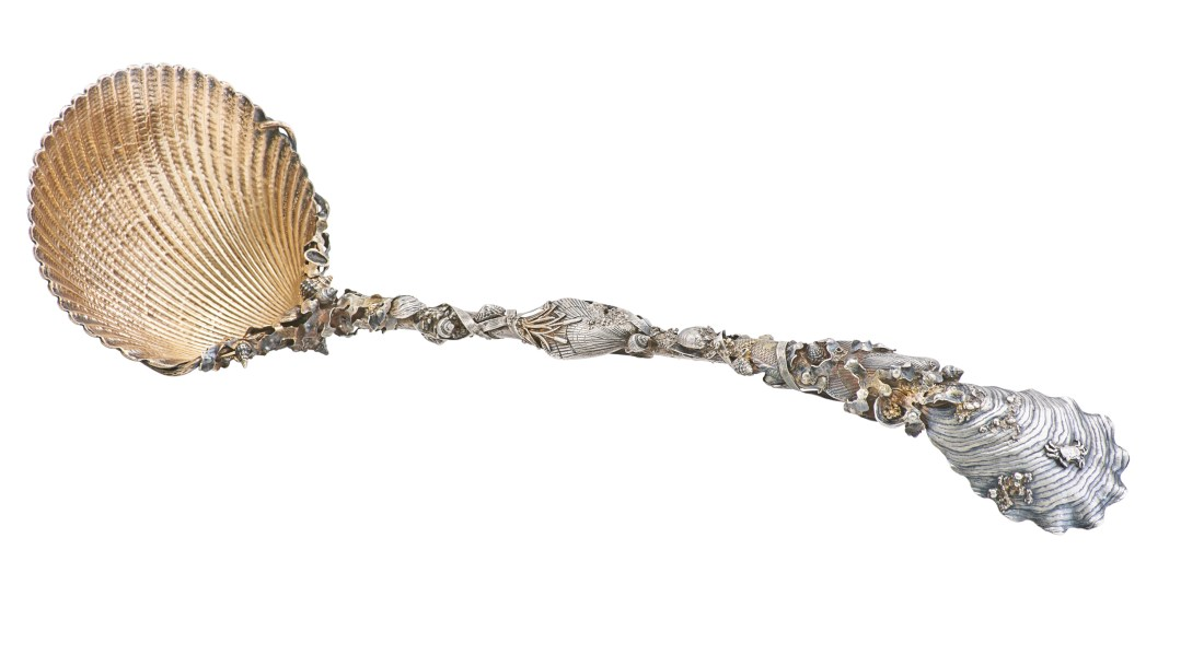 This circa 1880s parcel gilt sterling silver punch ladle in the Narragansett pattern by Gorham has a shell-shaped spoon that truly resembles a cockle shell. The interior of the spoon is gold. The stem of the ladle is festooned with with seaweed, fish, and grains of sand. The top of the handle resembles an oyster shell.