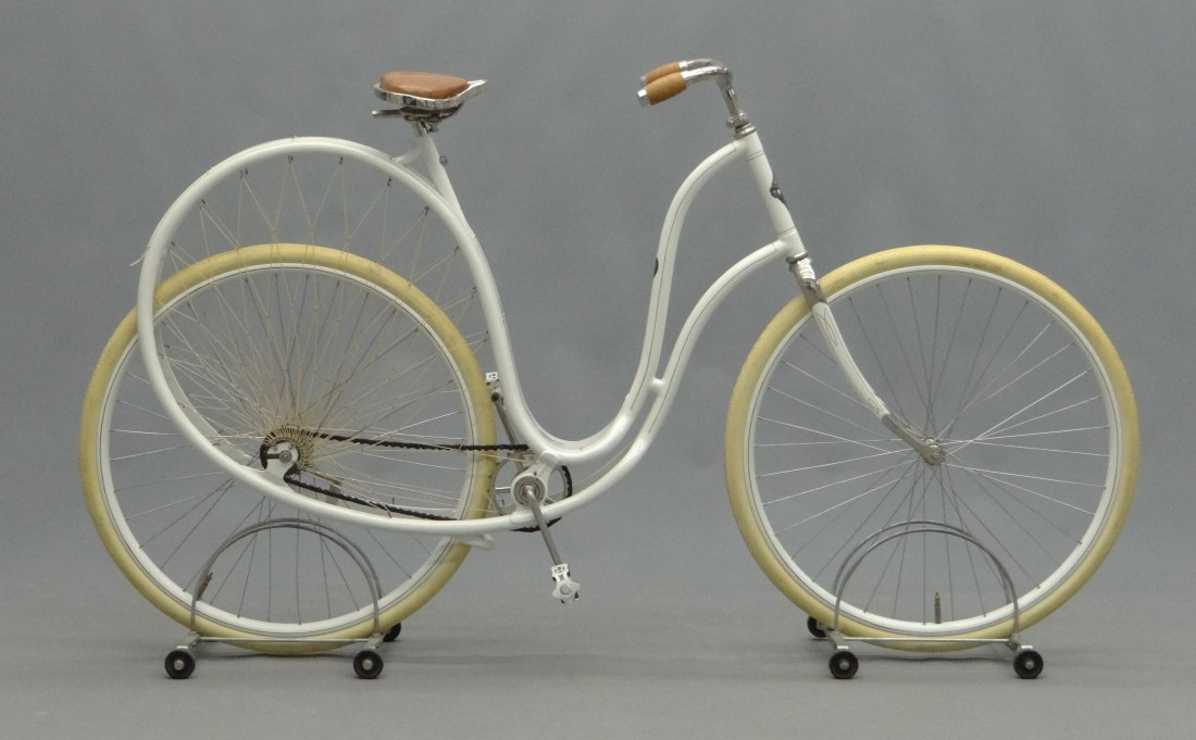 """An 1898 Cygnet """"Swan"""" Ladies pneumatic safety bicycle, which has a striking looped frame painted in white."""