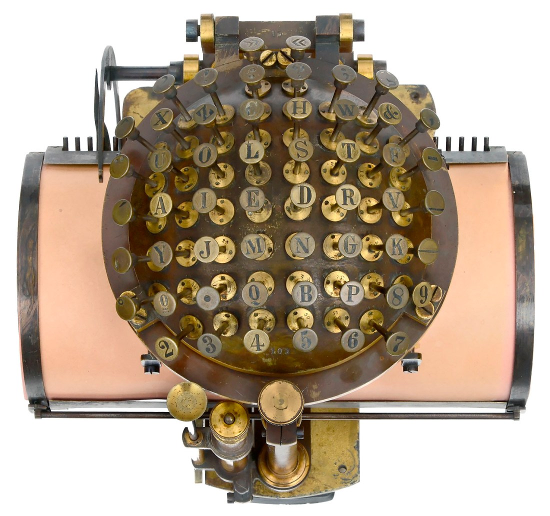 """An overhead view of a Malling-Hansen """"Writing Ball"""", an early typewriter. The semi-circular keyboard appears above its curved typing surface."""