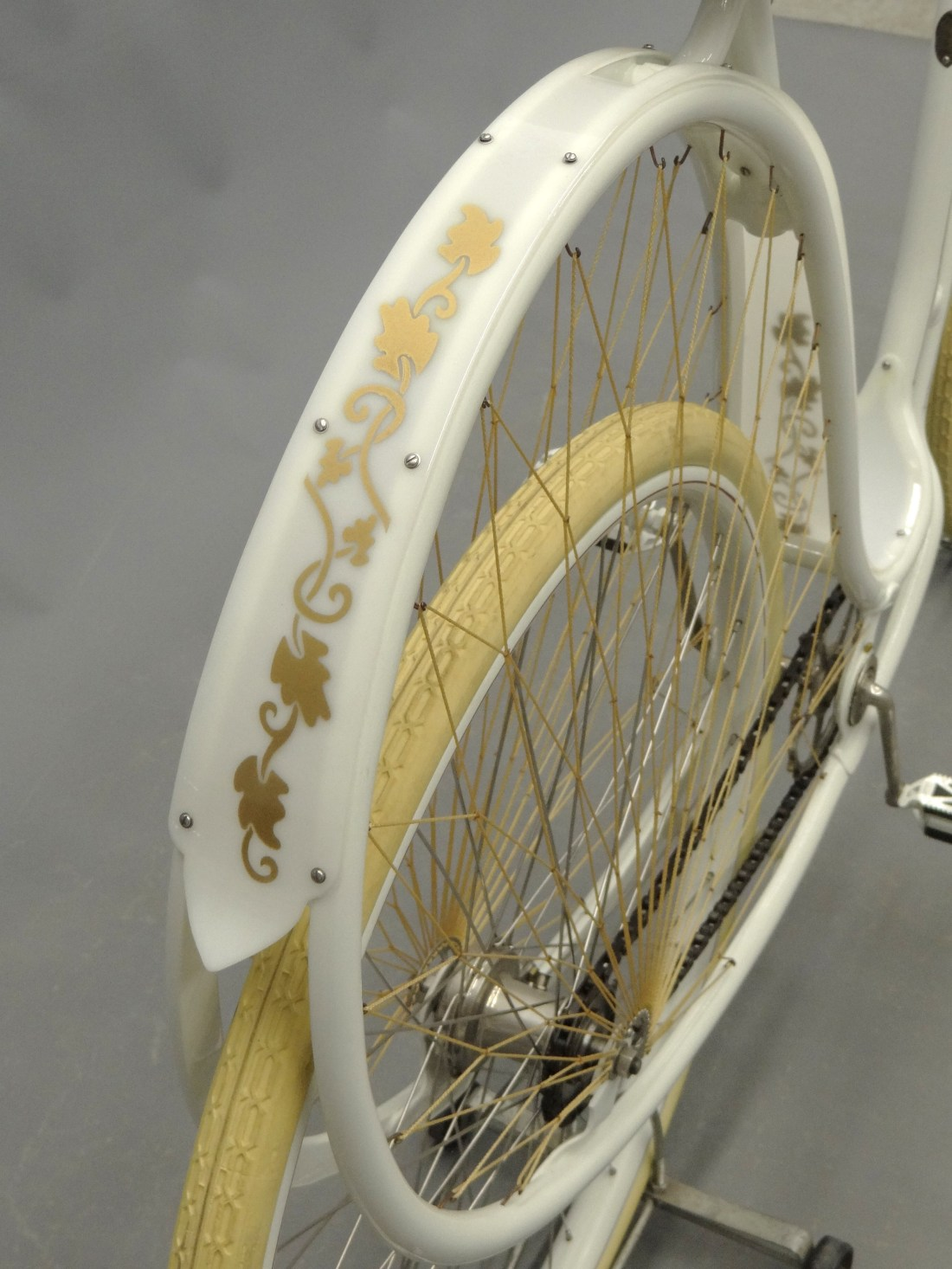 """A detail shot of the back wheel of the 1898 Cygnet """"Swan"""" Ladies pneumatic safety bicycle, which shows decorative gold vines painted on the back fender."""