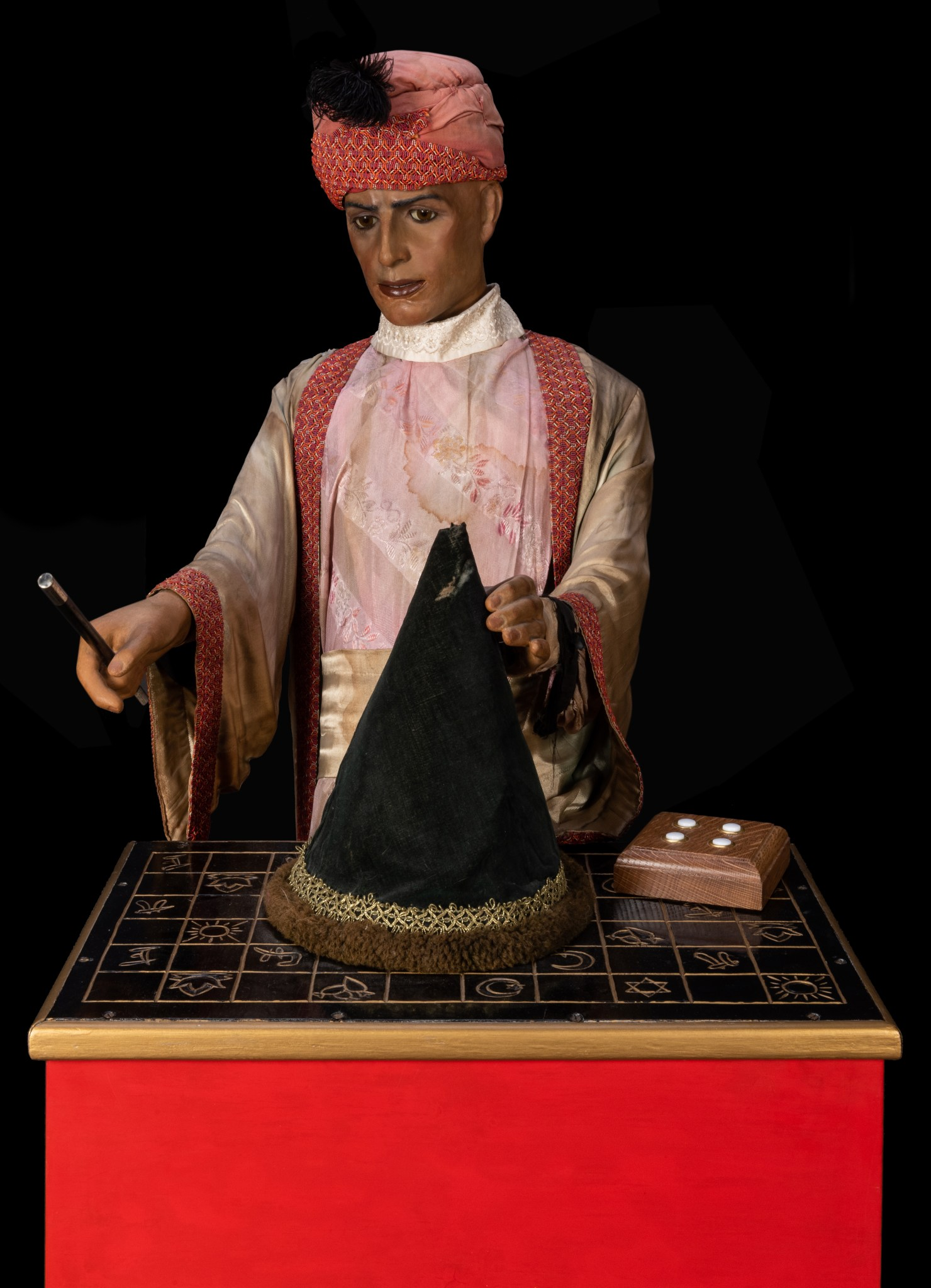 The magician automaton from Sleuth, shown head-on, about to lift a wizard's cap from a table carved with mysterious symbols.