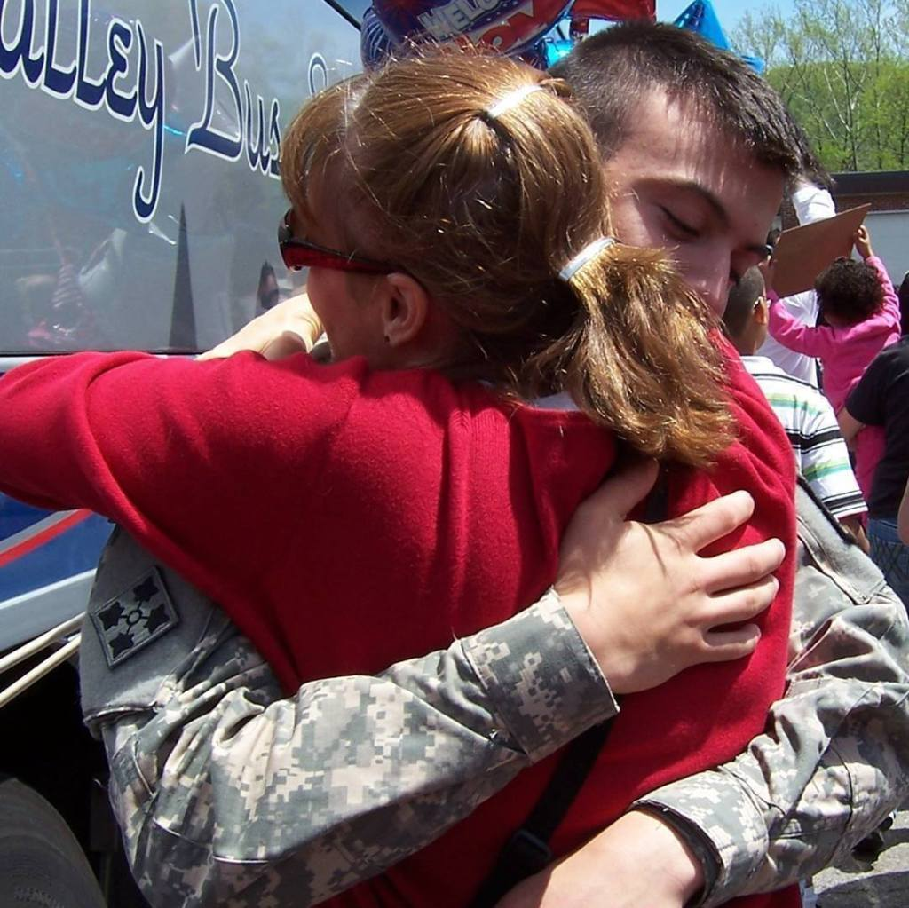wounded warrior, woman in red hugging soldier
